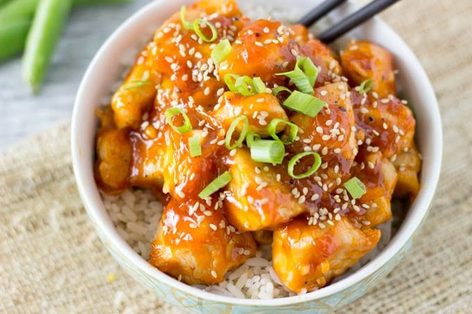 Overhead view of Healthy Orange Chicken over rice in a bowl with chopsticks