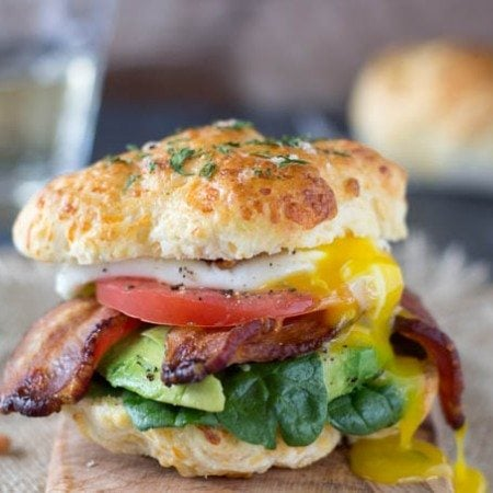 Ultimate Breakfast Sandwich- Fresh baked cheddar bay biscuits (low-fat and ready in 15 min.) take this breakfast sandwich to a whole new level! Topped with a poached egg , crispy bacon and healthy veggies like spinach, avocado and tomato
