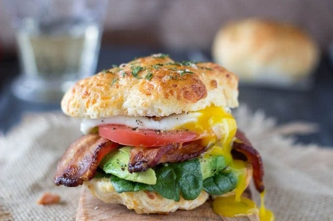 The Ultimate Breakfast Sandwich- Fresh baked cheddar bay biscuits (low-fat and ready in 15 min.) take this breakfast sandwich to a whole new level! Topped with a poached egg , crispy bacon and healthy veggies like spinach, avocado and tomato