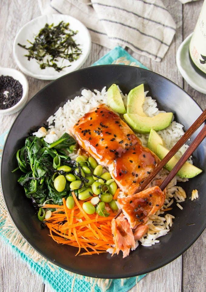 teriyaki salmon in a black bowl with edamame, shredded carrots and sauteed spinach