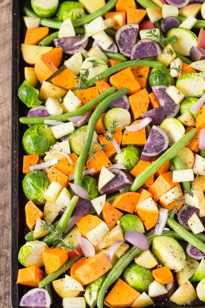 cut vegetables on a sheet pan ready to be oven roasted