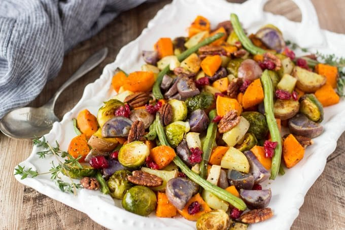 close up view of baked vegetables with pecans and dried cranberries on a white platter