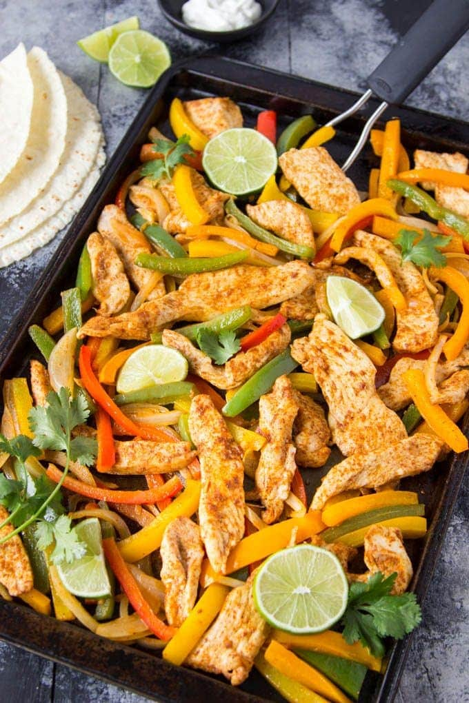 Healthy Sheet Pan Chicken Fajitas- Let the oven do the work! Only one sheet- pan and about 20 min needed to have tasty chicken fajitas on your table. Perfectly seasoned juicy chicken, bell peppers, and caramelized onions nestled in soft flour tortillas and topped with a squeeze of fresh lime and a sprinkling of fresh cilantro. A perfect weeknight meal the whole family will love.