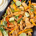 seasoned cooked chicken pieces with sliced red and yellow bell peppers on sheet pan