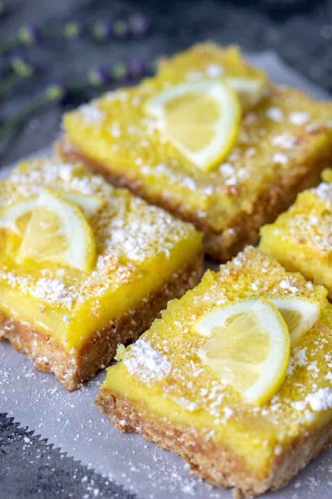 Healthy Lemon Bars - four lemon bars on a piece of parchment paper
