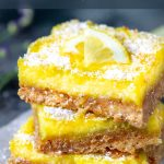 three lemon bars stacked on top of one another with a sprinkle of powdered sugar