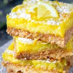 3 lemon bars stacked on top of one another and dusted with powdered sugar