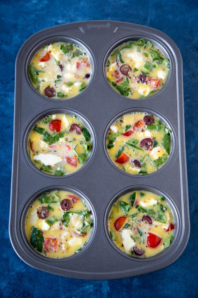 whipped eggs being added to Mediterranean vegetables in muffin tin to make egg cups (aka fritattas)