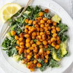 kale and romaine lettuce Caesar salad with crunchy Parmesan roasted chickpeas on a white plate