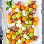 summer melons (honeydew and cantaloupe )balls and mozzarella balls with prosciutto on a white platter with serving spoon