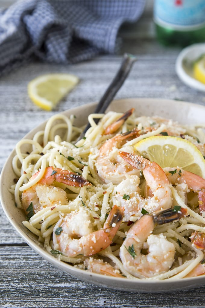 Close up photo of shrimp in a butter garlic sauce tossed with cooked spaghetti in a cream bowl garnished with fresh parsley and sliced lemons