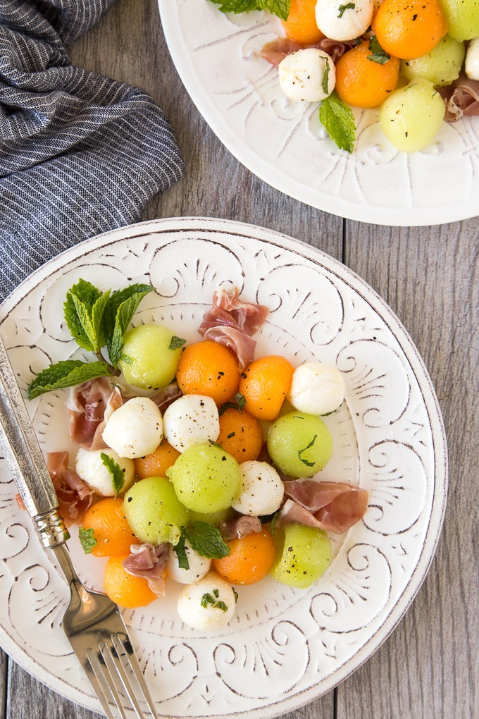 Summer Melon & Prosciutto Salad being served on individual white salad plates