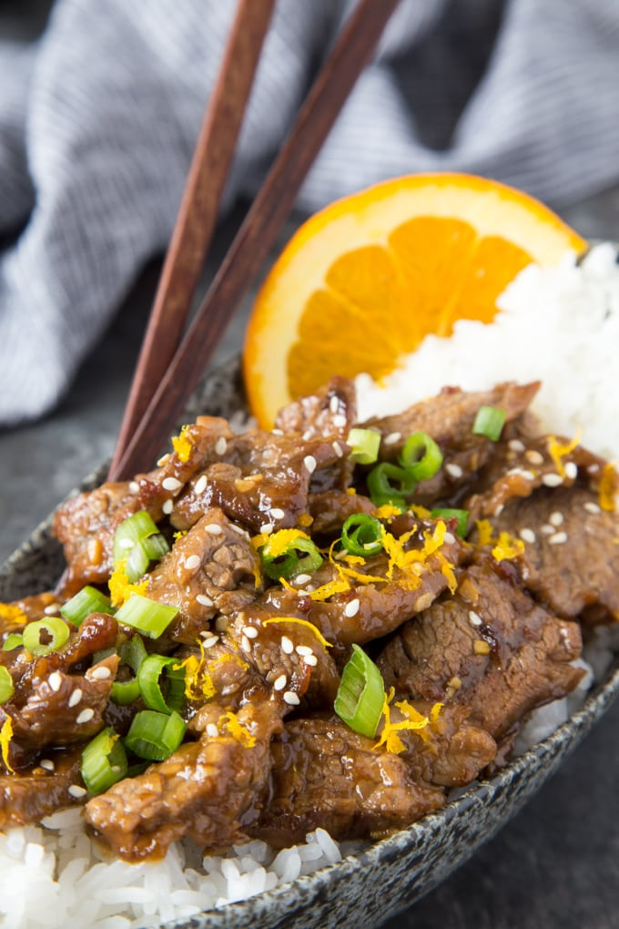 up close photo of  sesame orange beef over rice in a grey bowl