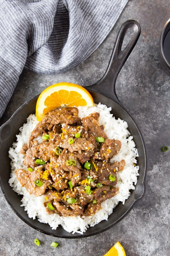 sesame orange beef over rice in a black skillet