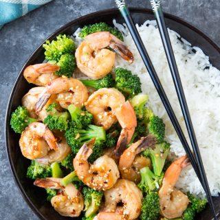 Skillet Honey Garlic Shrimp with broccoli in a black bowl over white rice