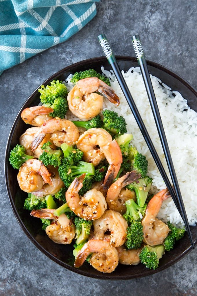 Skillet Honey Garlic Shrimp with broccoli served over white rice in a black bowl with chopsticks