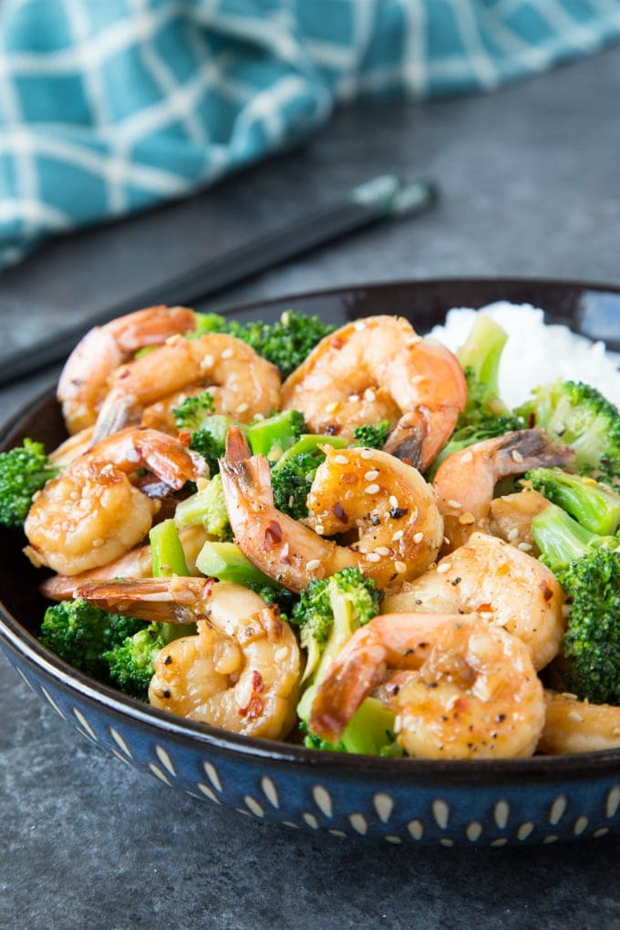 Skillet Honey Garlic Shrimp in a blue bowl with broccoli served over rice