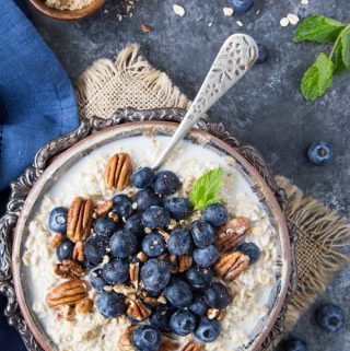 Oatmeal in a fancy silver bowl topped with fresh blueberries and chopped pecans