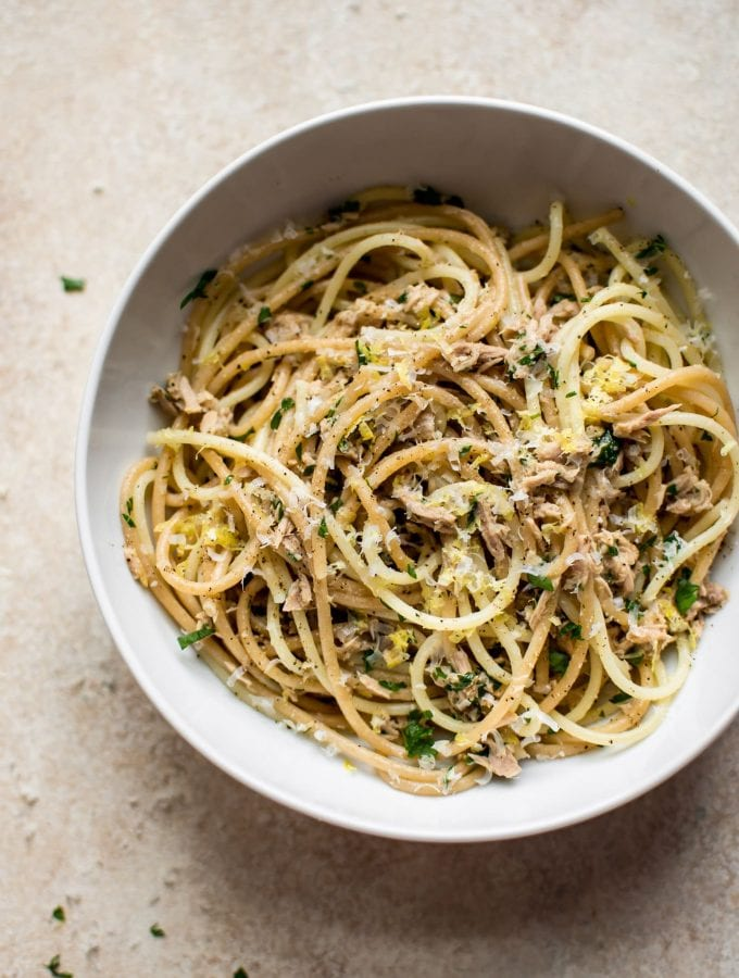 pasta with canned tuna and parsley in a cream bowl