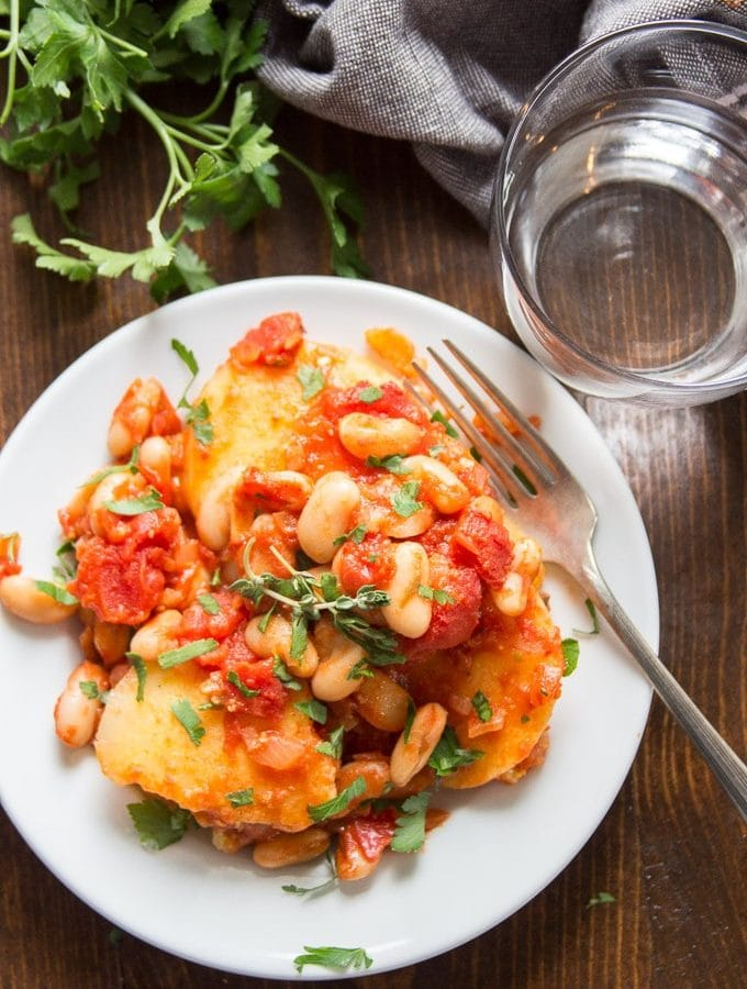 slices of polenta covered in tomatoes and white beans on a white plate