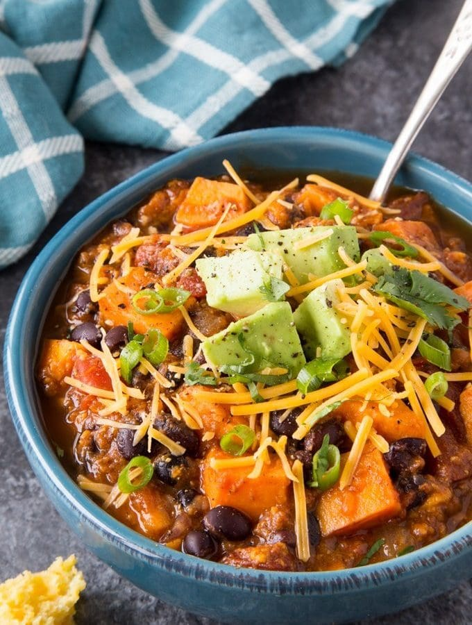 chili made with black beans, sweet potatoes and tomatoes in a blue bowl topped with shredded cheese, avocado and onion