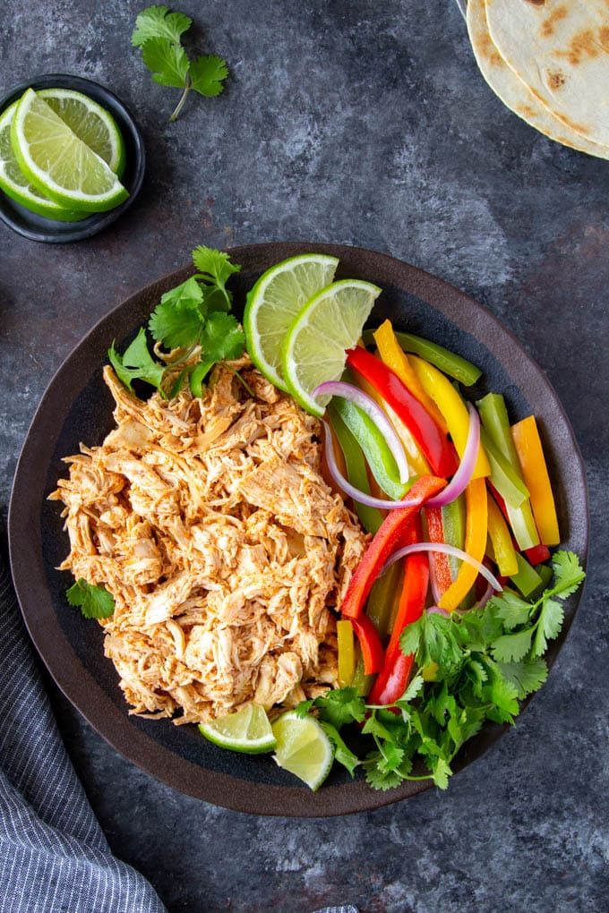 shredded chicken, bell peppers and onions on a plate ready to make fajitas