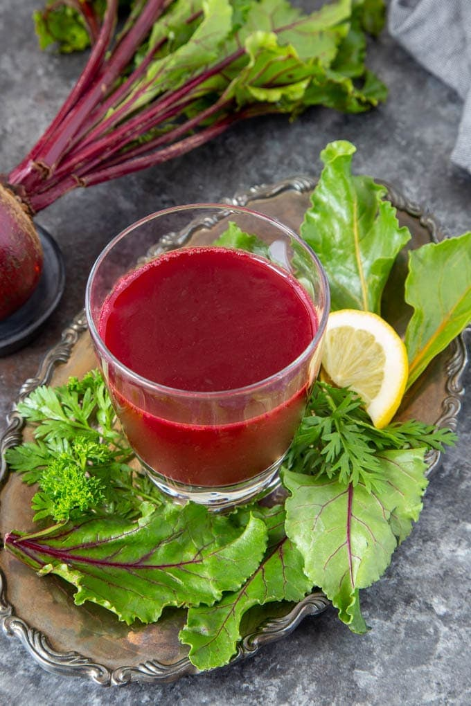 Bright red beet juice blend in clear glass on a silver serving platter