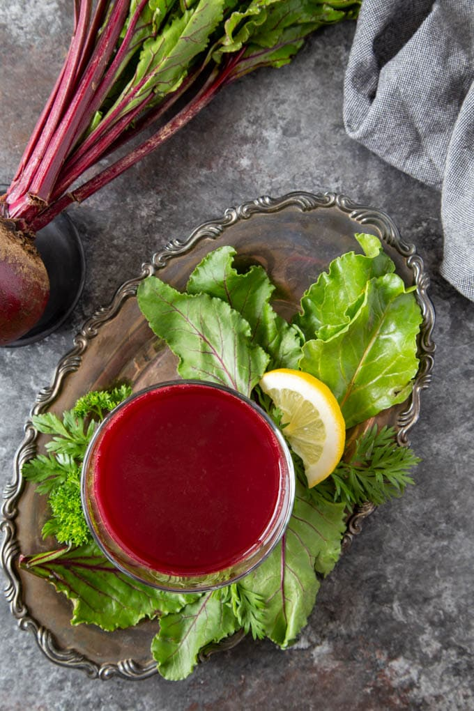 overhead view of bright red juice blend in a clear glass on a silver serving platter