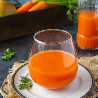fresh carrot apple juice in a clear glass
