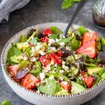 spinach salad with strawberries, avocado and quinoa in a white bowl with black fork
