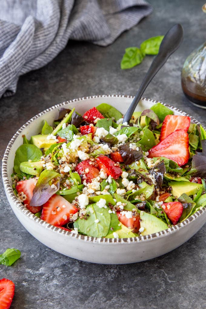 colorful red strawberries top a spinach salad with feta, avocado, quinoa and fresh chopped basil in a white bowl with black serving utensils.
