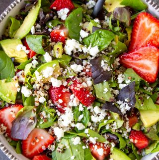 spinach salad with quinoa strawberries and feta up close in a white bowl