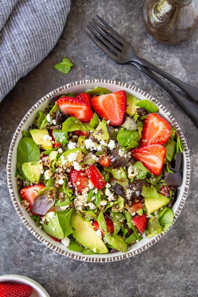 Strawberry Spinach Salad in a bowl next to a jar of homemade balsamic vinaigrette