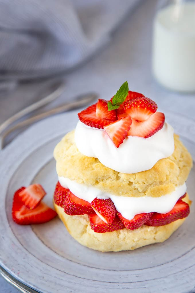 golden brown shortcake biscuits layered with sliced strawberries and whipped cream