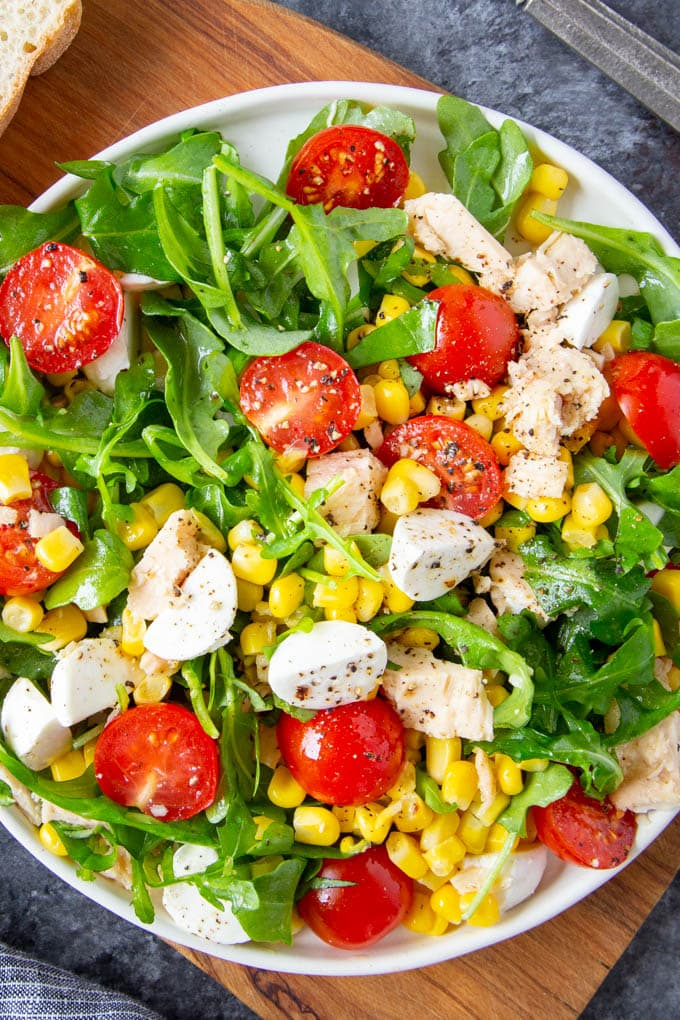 Close up photo of Italian Tuna salad on a white plate featuring fresh arugula, tomatoes, corn and mozzarella cheese