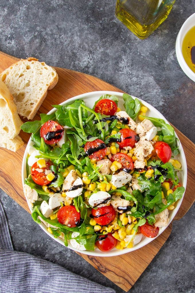 Tuna salad with fresh arugula, cherry tomatoes, corn, mozzarella cheese and basil on a white plate drizzled with balsamic glaze