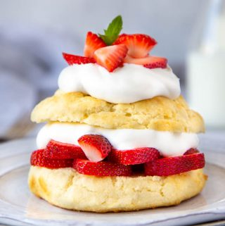 golden brown shortcake sliced in half and layered with slice strawberries and whipped cream.