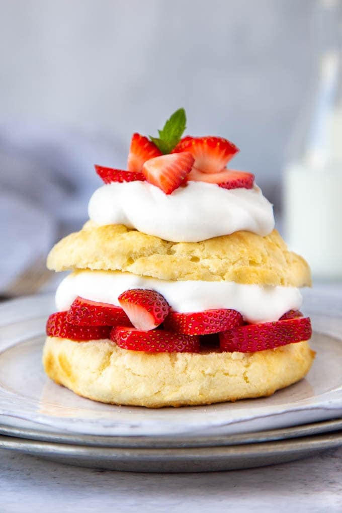 shortcakes layered with sliced strawberries and whipped cream served on a white plate