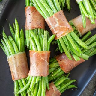 Green Bean Bundles stacked on a black serving tray