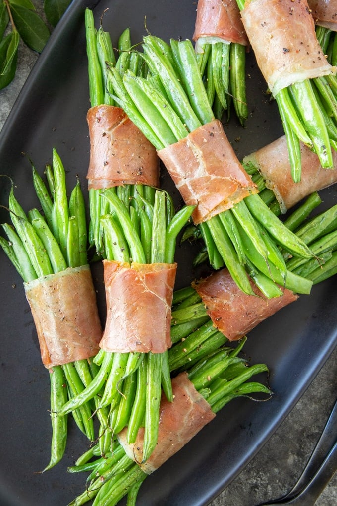 Roasted green bean bundles wrapped in prosciutto and stacked on a black serving tray